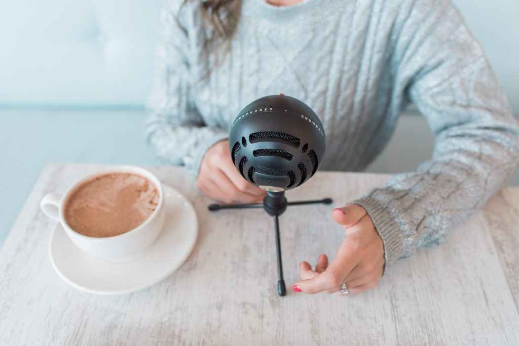 good podcasts to listen to, top favourite podcasts, 8 podcasts to listen to. Podcaster with microphone and coffee